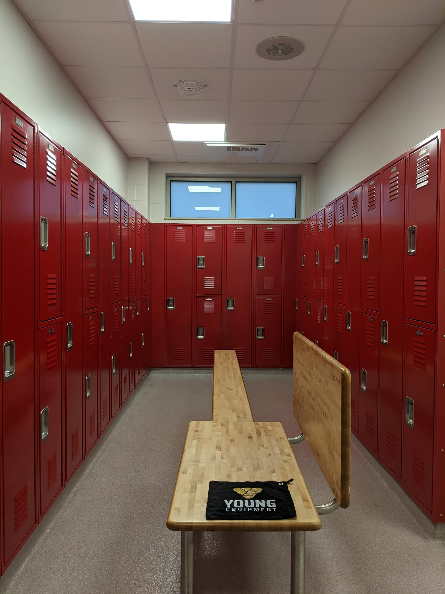 Red two tier and full length alternating metal lockers with large bench.