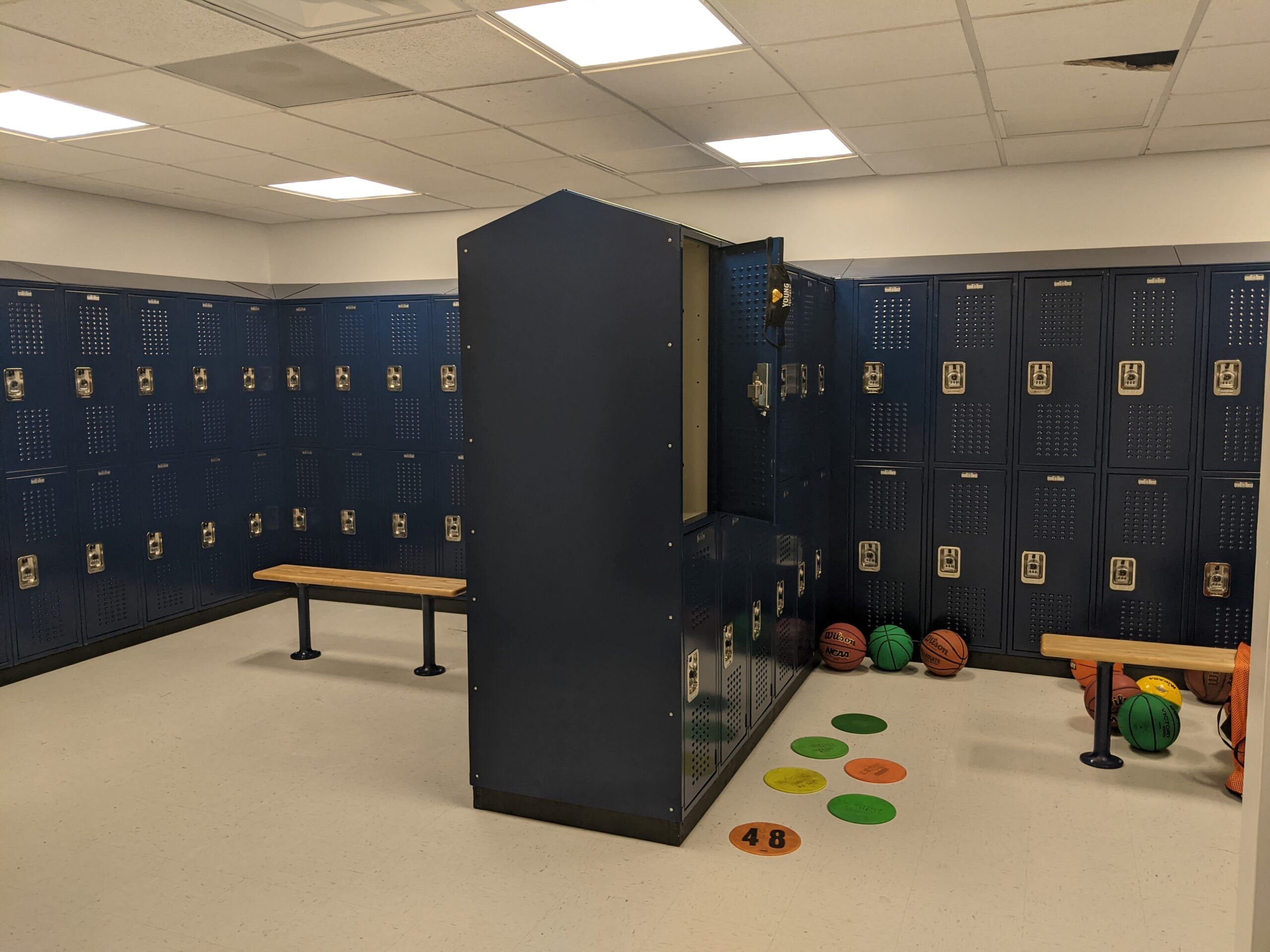 Blue two tier lockers with basketballs and one locker open