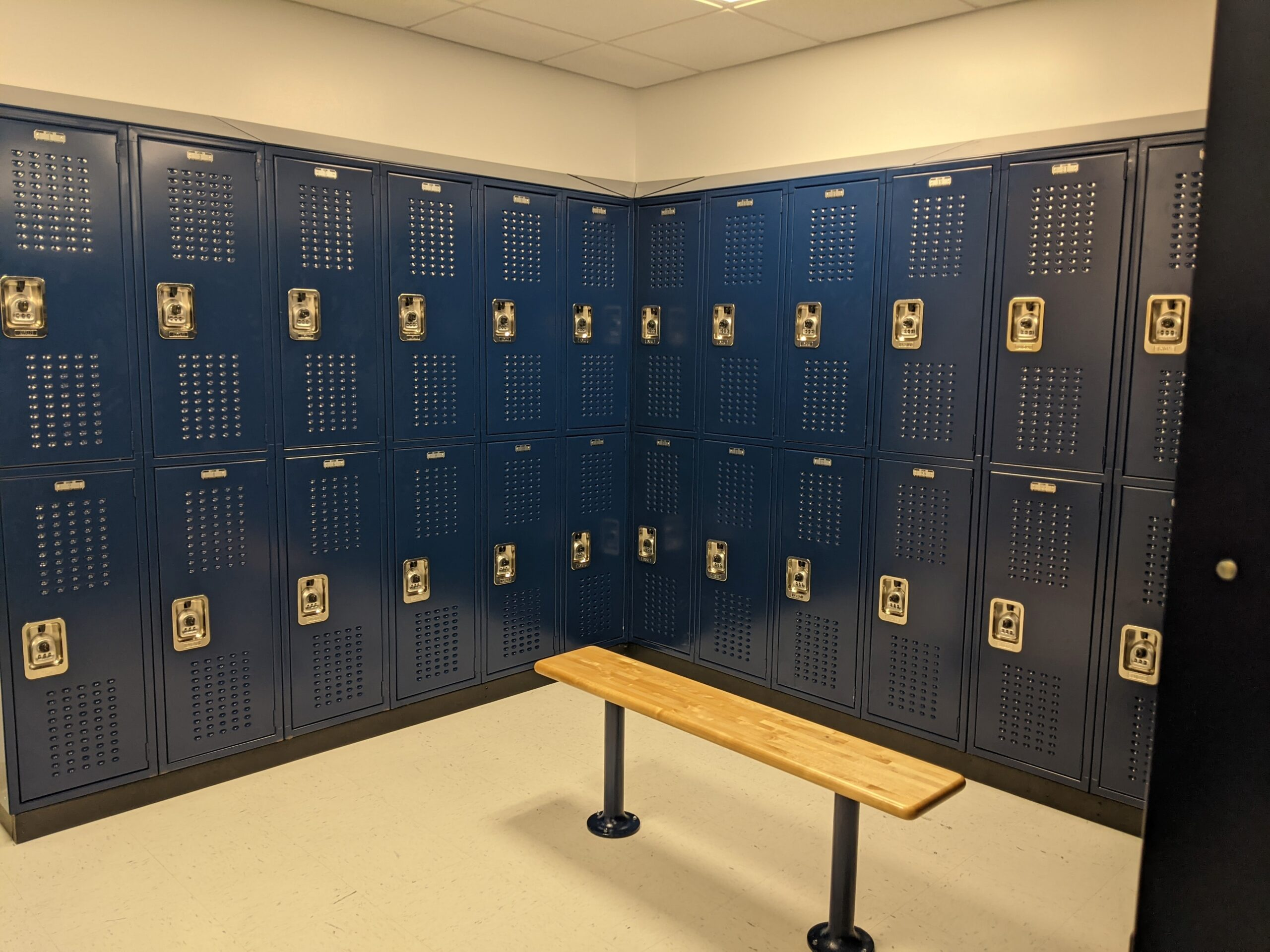 Blue vented two tier lockers at UNIS with a bench
